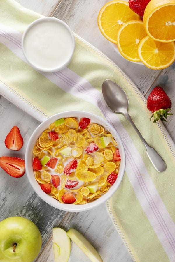 早餐玉米片和草莓用牛奶、酸奶和橙汁过去 免版税库存照片