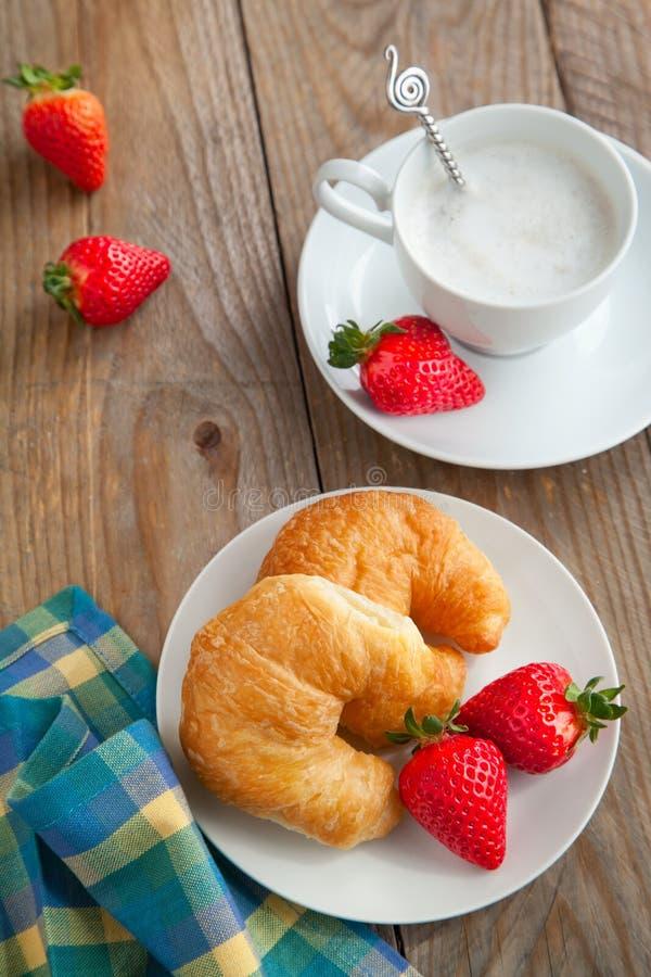 早餐用咖啡和新鲜的新月形面包 免版税图库摄影