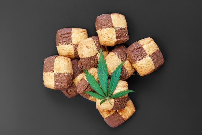 早餐用在黑暗的背景的甜曲奇饼与大麻一片绿色叶子  大麻CBD点心 r E 免版税库存照片