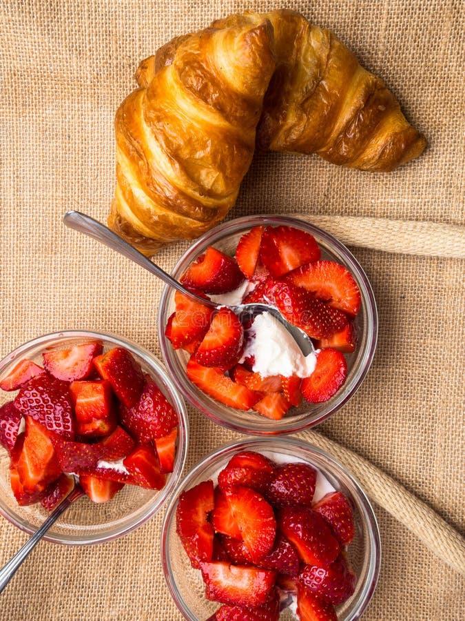 早餐用新鲜的新月形面包,与奶油的草莓在玻璃碗背景中 免版税库存图片