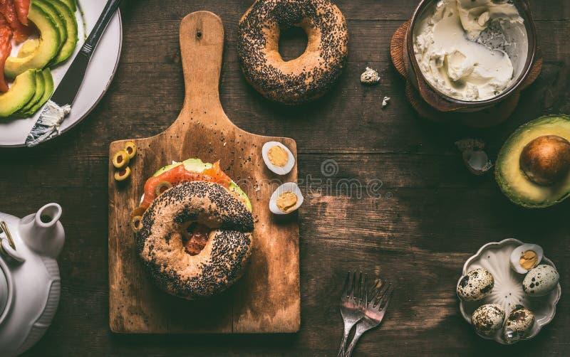 早餐用百吉卷面包冠上与三文鱼、鲕梨和新鲜的干酪在黑暗的土气木背景,顶视图 免版税库存图片