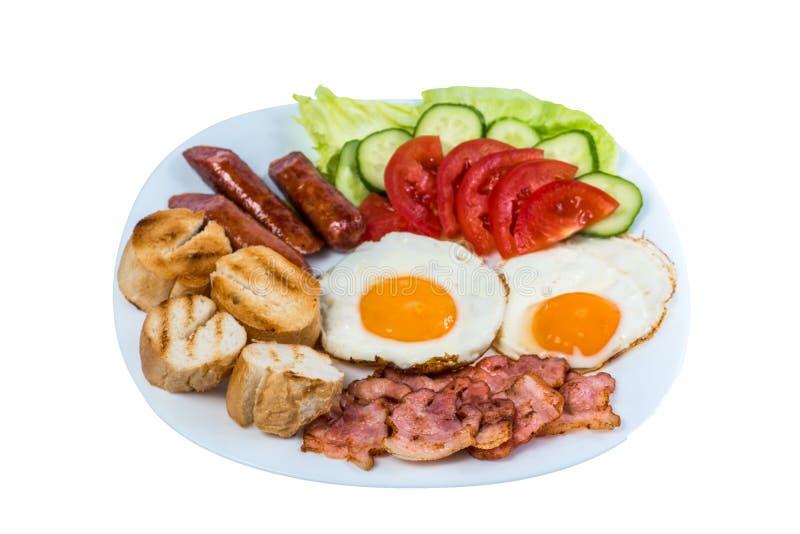 早餐荷包蛋新鲜蔬菜油煎了烟肉、油煎的香肠和橄榄在一块白色板材 图库摄影
