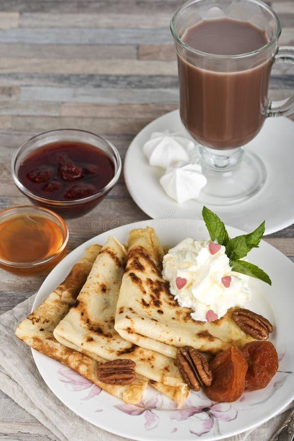 早餐薄煎饼、蜂蜜、草莓酱、奶油、杏干、坚果和巧克力热饮或者可可粉或者咖啡 库存照片