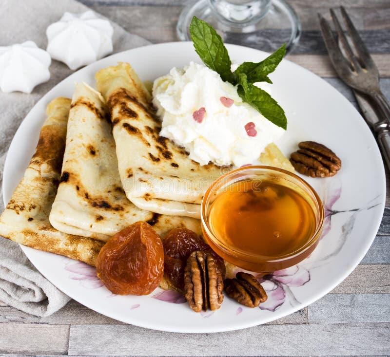 早餐薄煎饼、蜂蜜、草莓酱、奶油、杏干、坚果和巧克力热饮或者可可粉或者咖啡 免版税库存照片