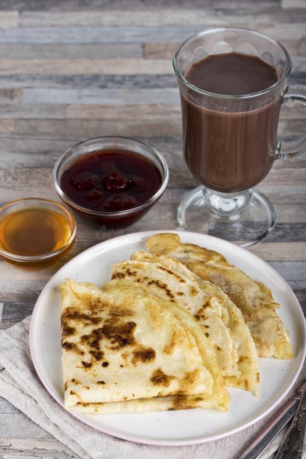 早餐薄煎饼、蜂蜜、草莓酱、奶油、杏干、坚果和巧克力热饮或者可可粉或者咖啡 免版税库存图片