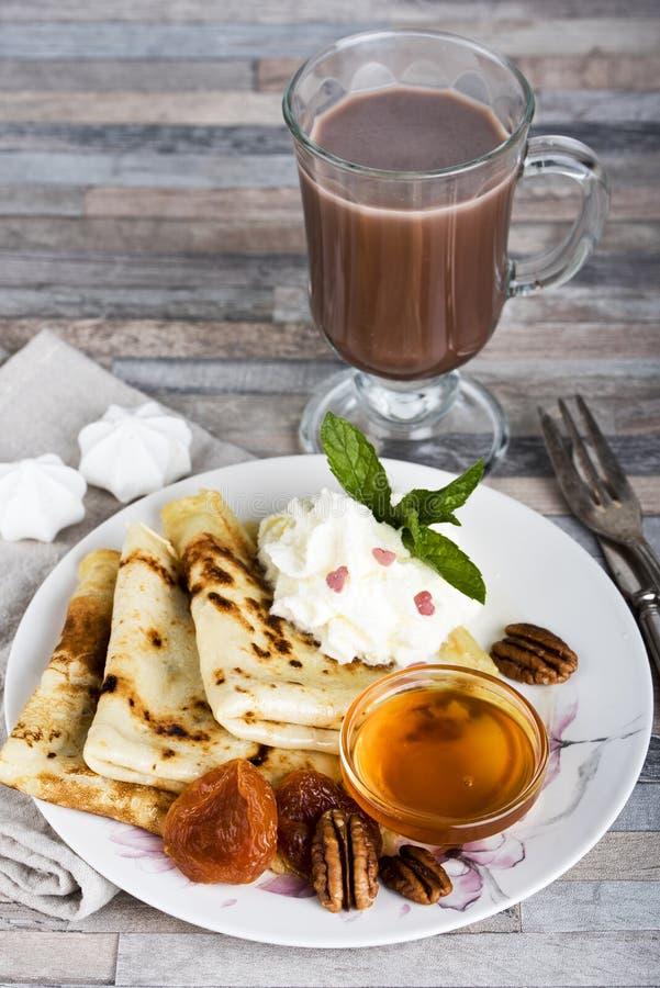 早餐薄煎饼、蜂蜜、草莓酱、奶油、杏干、坚果和巧克力热饮或者可可粉或者咖啡 图库摄影