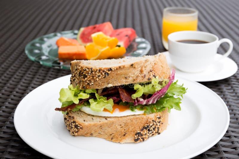 早餐设置了用煎蛋三明治和咖啡和橙色jui 库存图片