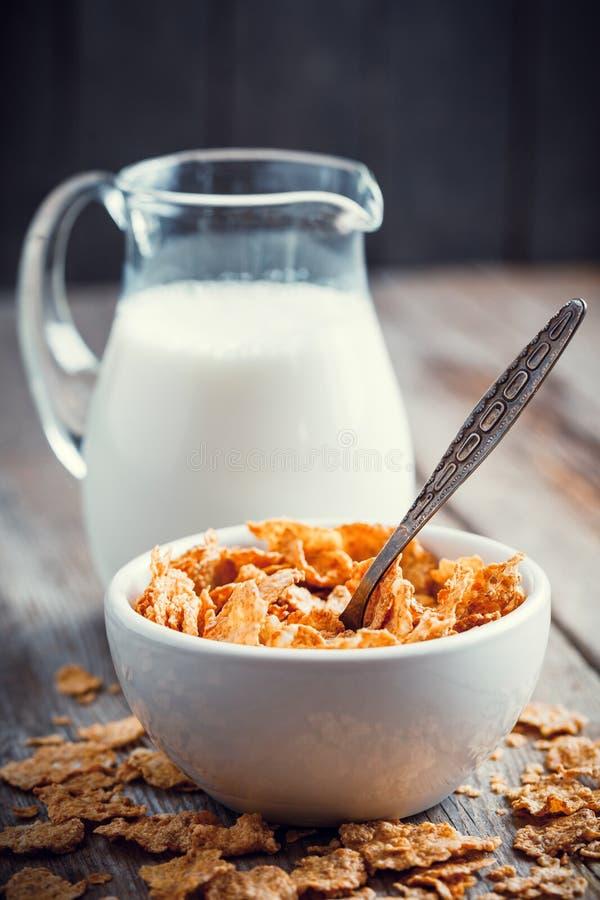 早餐谷物麦子在碗和牛奶罐剥落 免版税图库摄影