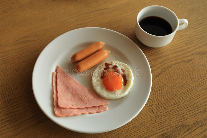 早餐集合、煎蛋、火腿、香肠和杯子无奶咖啡 图库摄影