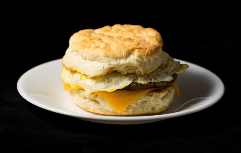早餐香肠鸡蛋和乳酪饼干在黑背景 图库摄影