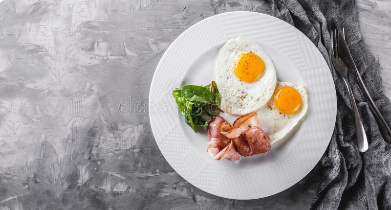 早餐,荷包蛋,烟肉,熏火腿,在板材的新鲜的沙拉灰色桌表面上 健康食物,顶视图,平的位置 免版税库存图片
