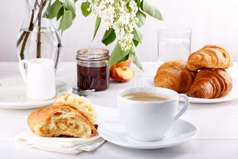 早餐-咖啡、新月形面包、果酱和果子在白色桌上 库存图片