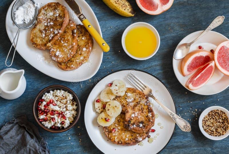 早餐-焦糖法式多士用香蕉、酸奶干酪与格兰诺拉麦片和石榴,新鲜的葡萄柚在蓝色背景 免版税库存图片