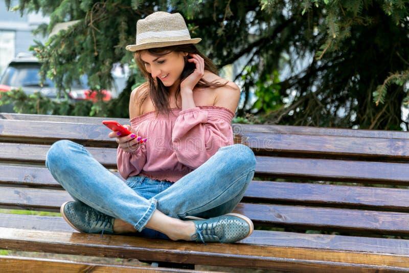 时兴地在街道上的加工好的年轻女人在一个晴朗的晚上 牛仔裤、女衬衫和一个小帽子的女孩坐长凳和 库存图片
