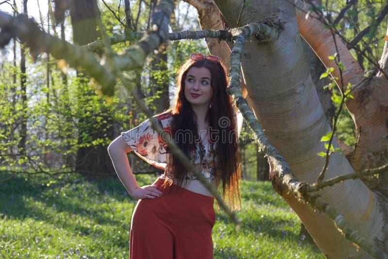 时兴地摆在与一棵白桦树树的加工好的夫人 图库摄影