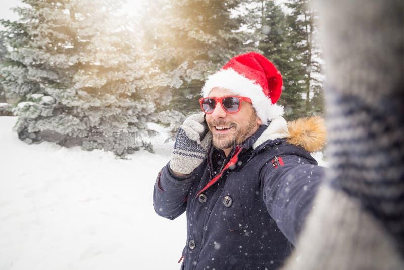 时兴的人采取selfie和谈话在手机在山的多雪的天期间 免版税库存照片