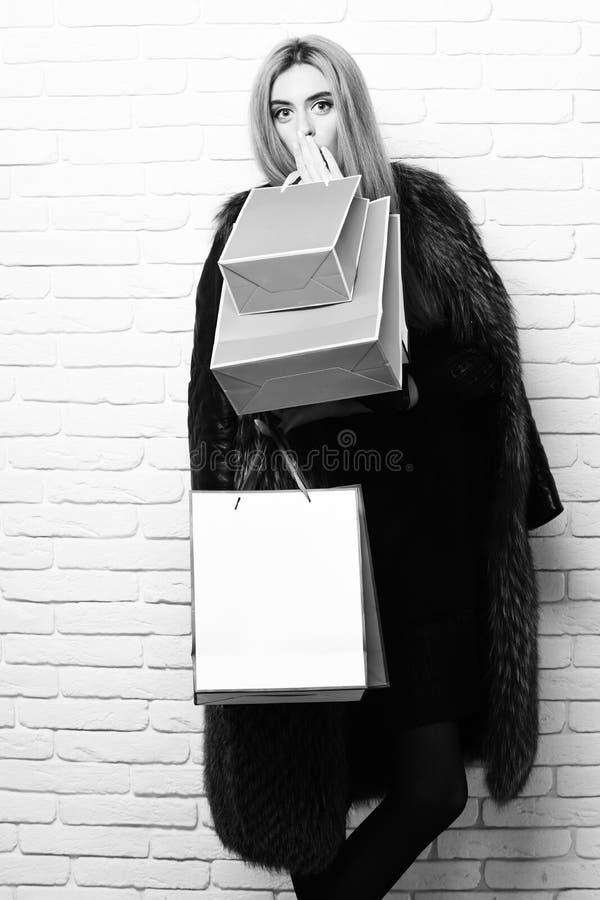 时兴的俏丽的妇女或女孩有美丽的金发的在伯根地毛皮腰部外套与黑礼服和 免版税库存图片