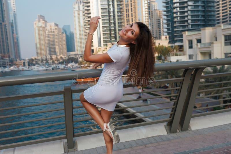 时兴的夏天白色礼服的愉快的美丽的旅游妇女走和享用在迪拜小游艇船坞的在阿拉伯联合酋长国 免版税图库摄影