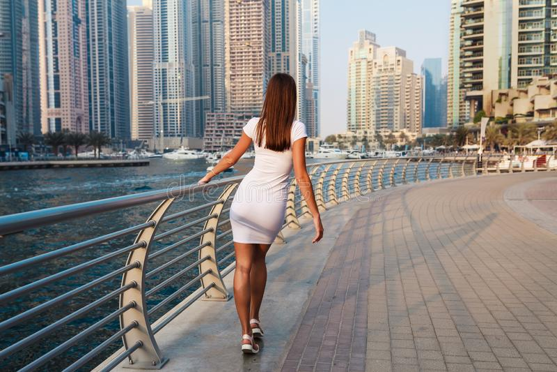 时兴的夏天白色礼服的愉快的美丽的无法认出的旅游妇女享用在迪拜小游艇船坞的在阿拉伯联合酋长国 库存图片