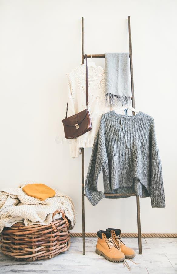 时兴的女性冬天衣物和起动在whate墙壁背景 图库摄影
