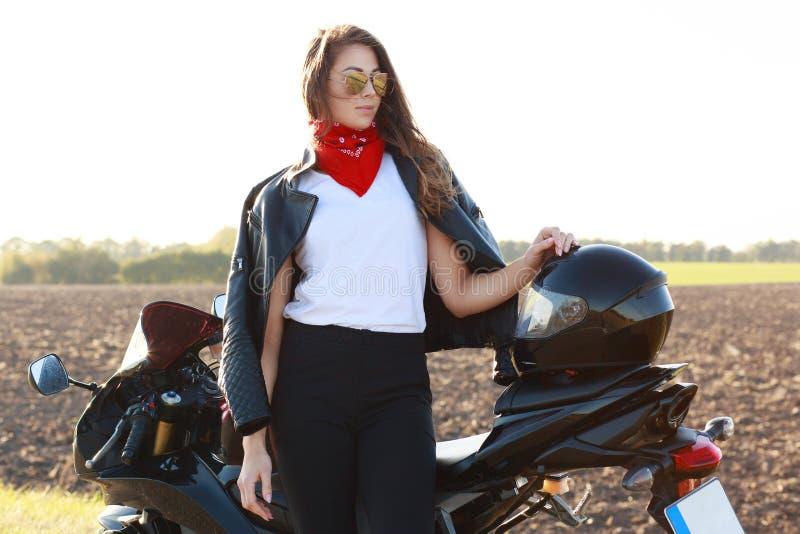 时兴的女性骑自行车的人水平的射击穿皮夹克,太阳镜,红色班丹纳花绸,在快速的motorrbike,用途盔甲附近摆在 免版税库存照片