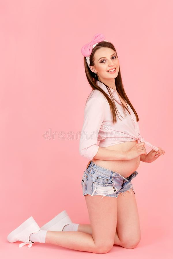 时兴的年轻怀孕的女孩在桃红色背景的演播室 库存照片