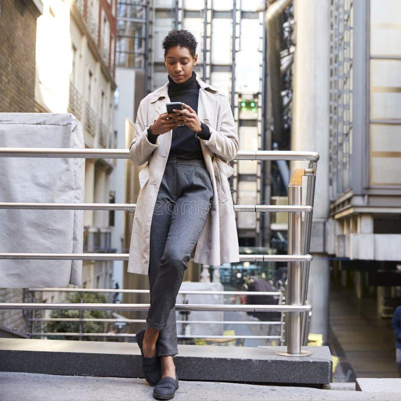 时兴的年轻黑人妇女身分在倾斜在扶手的城市使用她的智能手机,全长,低角度 免版税库存图片