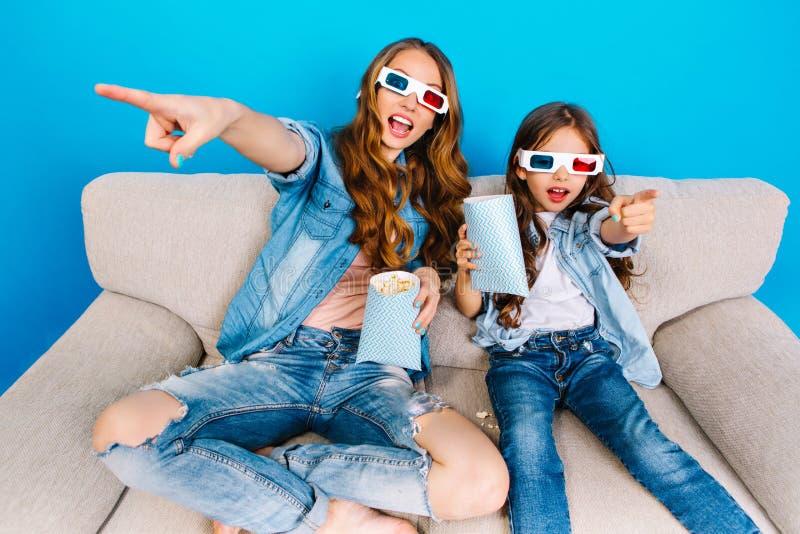 时兴的快乐的牛仔裤衣裳的吃玉米花,电影的母亲和她的女儿在3D玻璃在长沙发 免版税库存图片