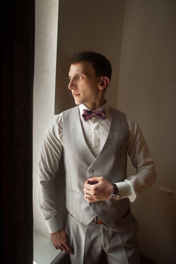 时兴的新郎在窗口附近等新娘 新郎的画象一件灰色背心的 免版税图库摄影