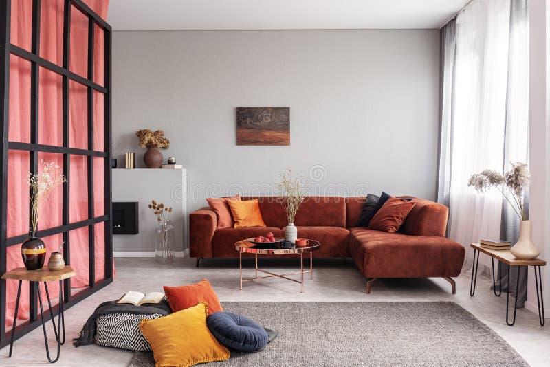 时兴的有枕头的天鹅绒壁角沙发在与花的典雅的咖啡桌旁边 免版税库存图片