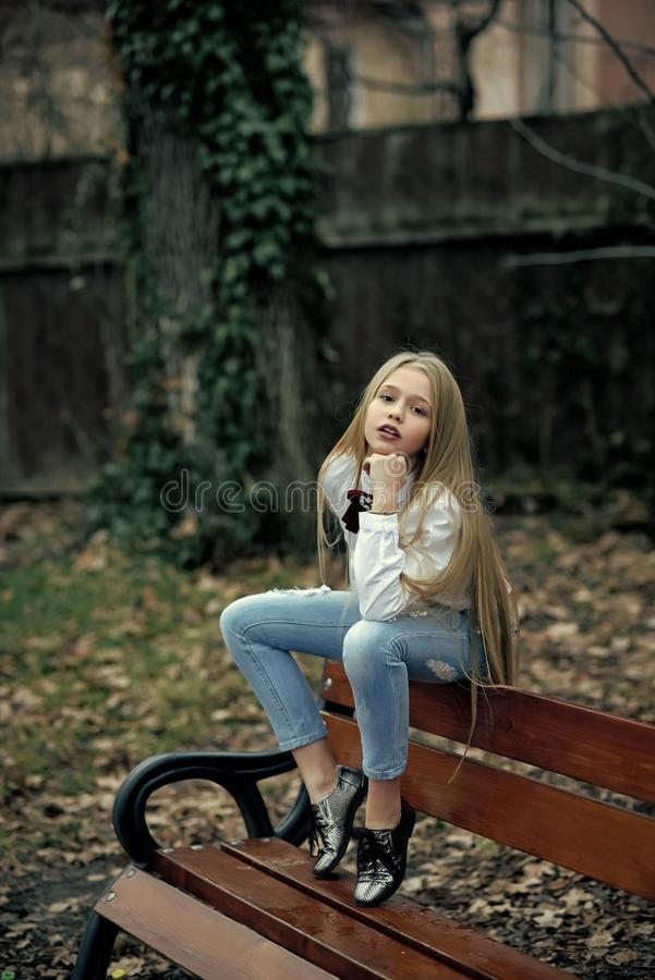 时兴的牛仔裤的女孩坐长凳,时尚 有长的金发的,发型室外秀丽小孩子 婴孩秀丽 免版税库存图片