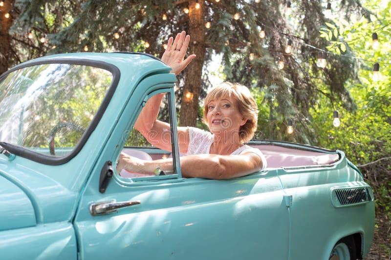 时兴的现代可爱的祖母在轮子减速火箭的汽车后坐 老人暑假和旅行  库存照片