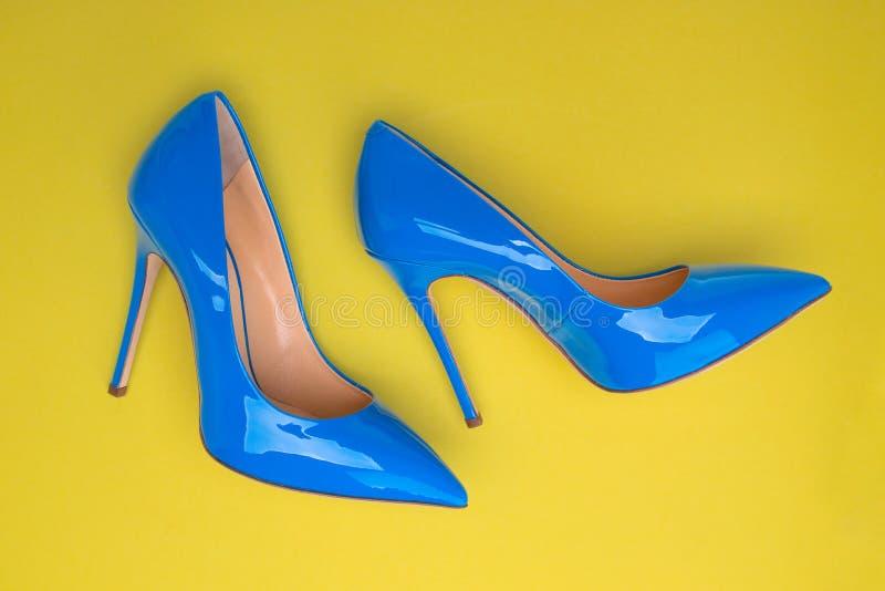 时兴的蓝色高跟鞋和黄色背景 免版税库存照片