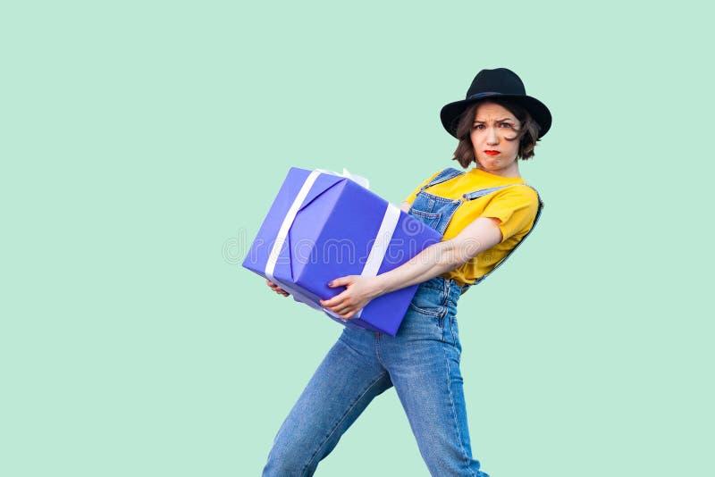 时兴的行家穿戴的迷茫的坚强的少女在牛仔布总体和黑帽会议身分和设法举行巨型大重 免版税图库摄影