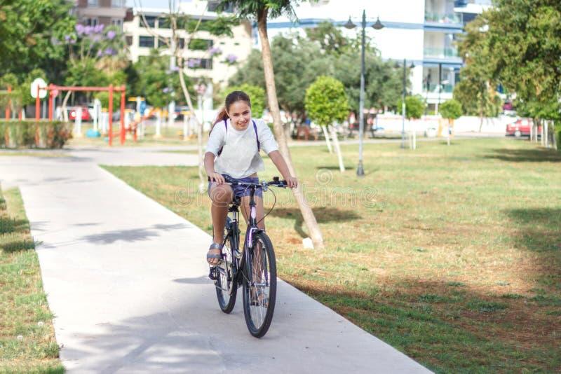 时兴的青少年女孩简而言之和T恤杉在夏天公园骑一辆自行车 图库摄影