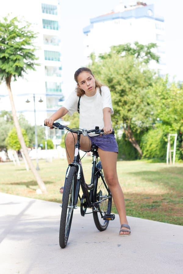 时兴的青少年女孩简而言之和T恤杉在夏天公园骑一辆自行车 库存照片