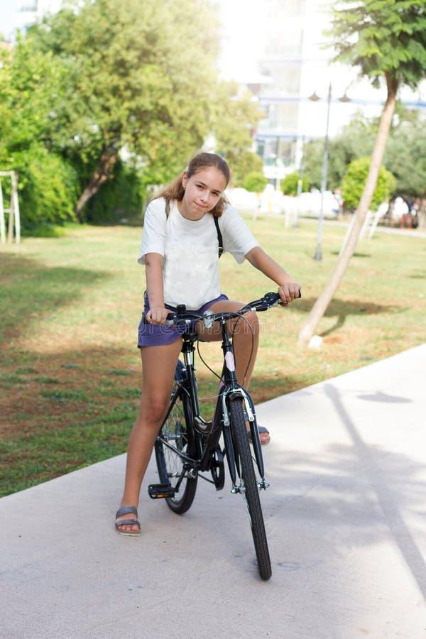 时兴的青少年女孩简而言之和T恤杉在夏天公园骑一辆自行车 免版税图库摄影