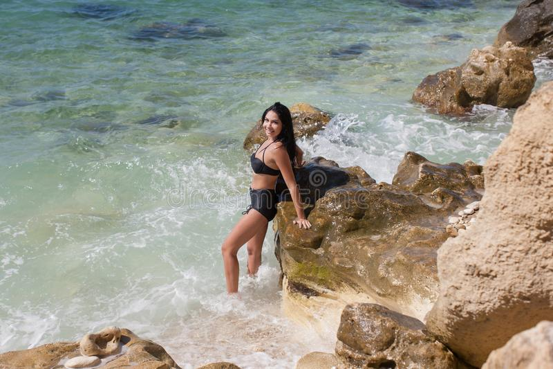 时兴的黑泳装的湿深色的女孩在辗压海 免版税库存照片