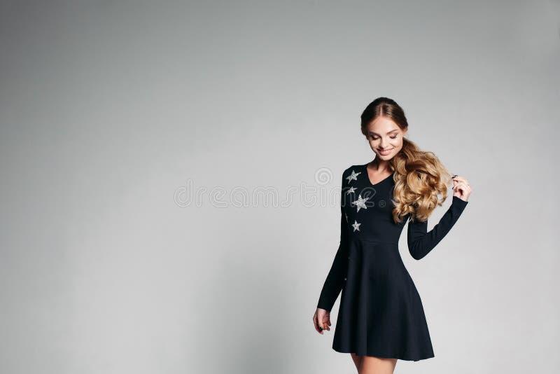 时兴的黑礼服的阳妇女有星跳舞的 图库摄影