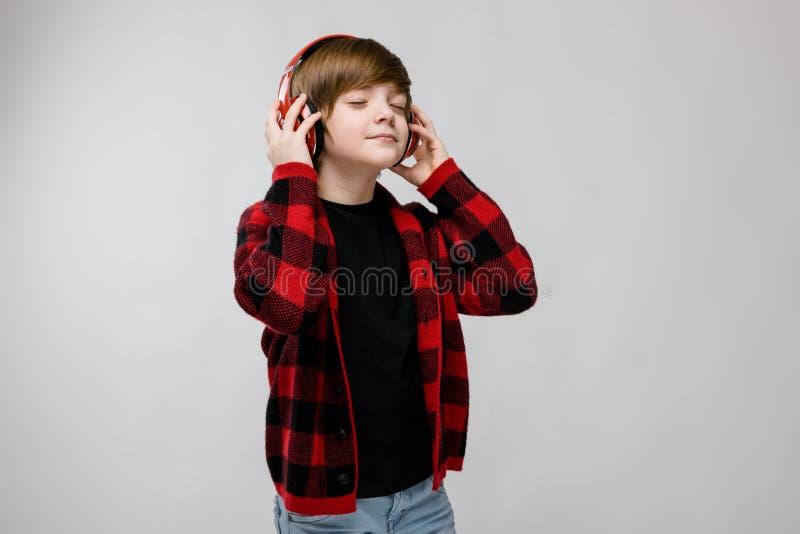 时兴的clother和耳机的十几岁的男孩 库存照片