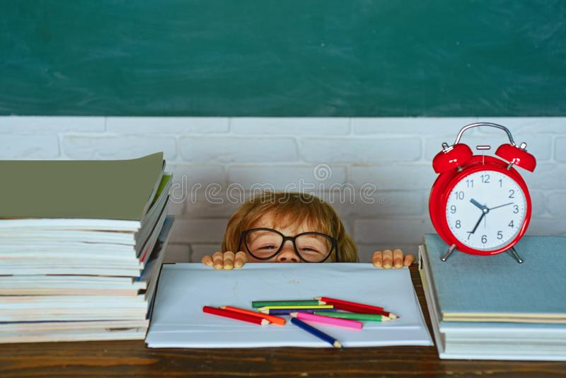 时刻学会概念 反对绿色黑板的学校孩子   教育过程 是的孩子晚为 库存图片
