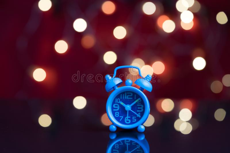 时刻醒工作,有党装饰的蓝色闹钟 免版税库存图片