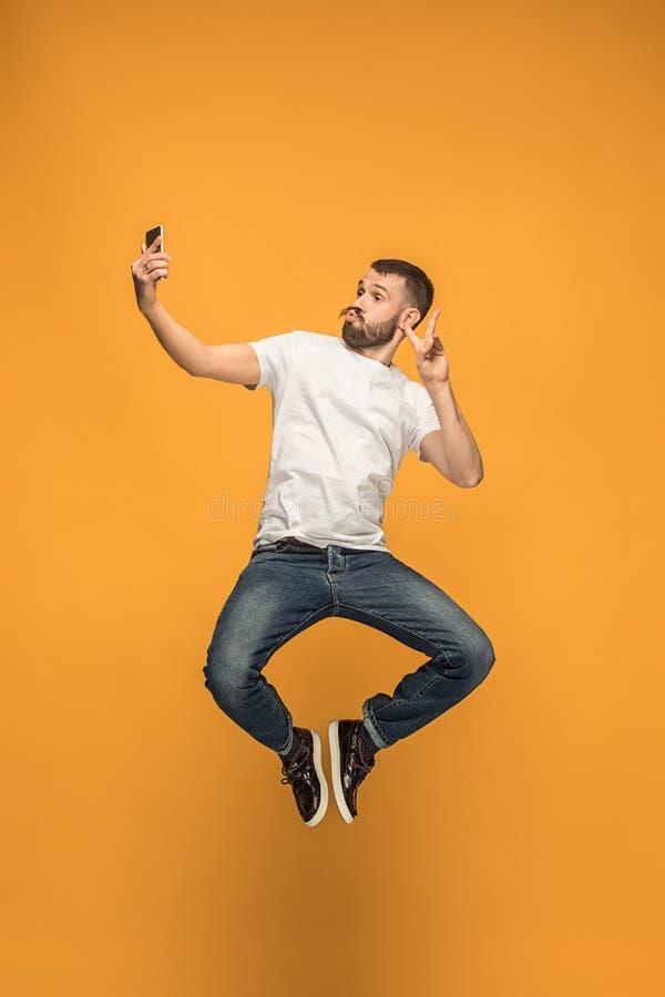 时刻采取selfie 采取selfie的全长英俊的年轻人,当跳跃时 免版税库存图片