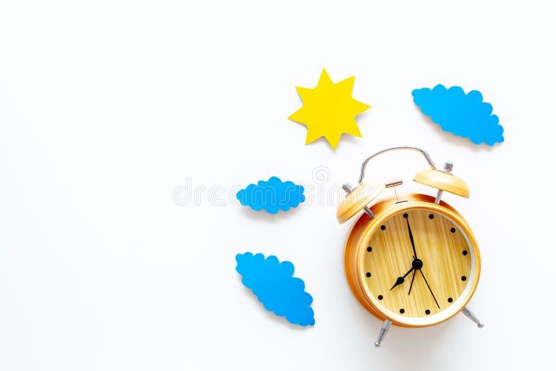 时刻 早晨 唤醒和日出 太阳和云彩保险开关在闹钟附近在白色背景顶视图复制 库存照片