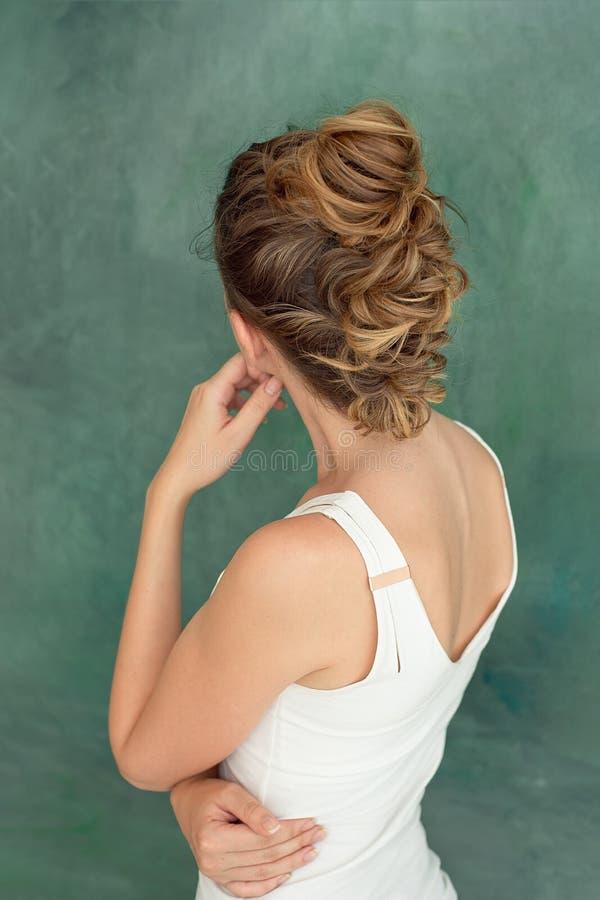 时尚一个美丽的深色的夫人的演播室画象有一种别致的发型的在一件白色女衬衫的eroquez样式 免版税库存图片