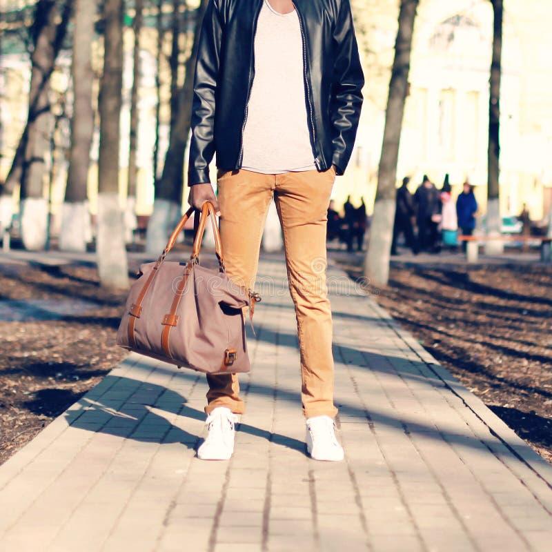 时尚人站立与在他的手户外特写镜头的一个袋子 免版税库存照片