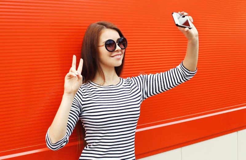时尚俏丽的女服太阳镜和镶边的礼服在红色的智能手机做自画象 免版税库存照片
