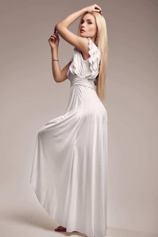 时尚古色古香的白色礼服的华美的肉欲的白肤金发的妇女 库存照片