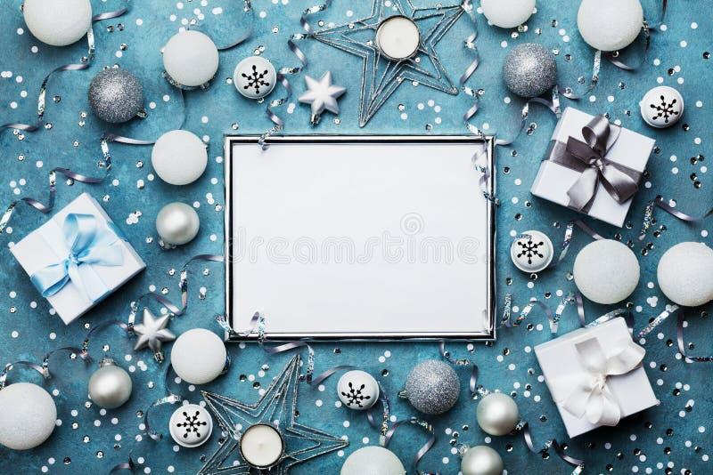 时尚圣诞节背景 与xmas装饰、礼物盒和衣服饰物之小金属片的银色框架 党大模型或欢乐邀请 免版税库存照片