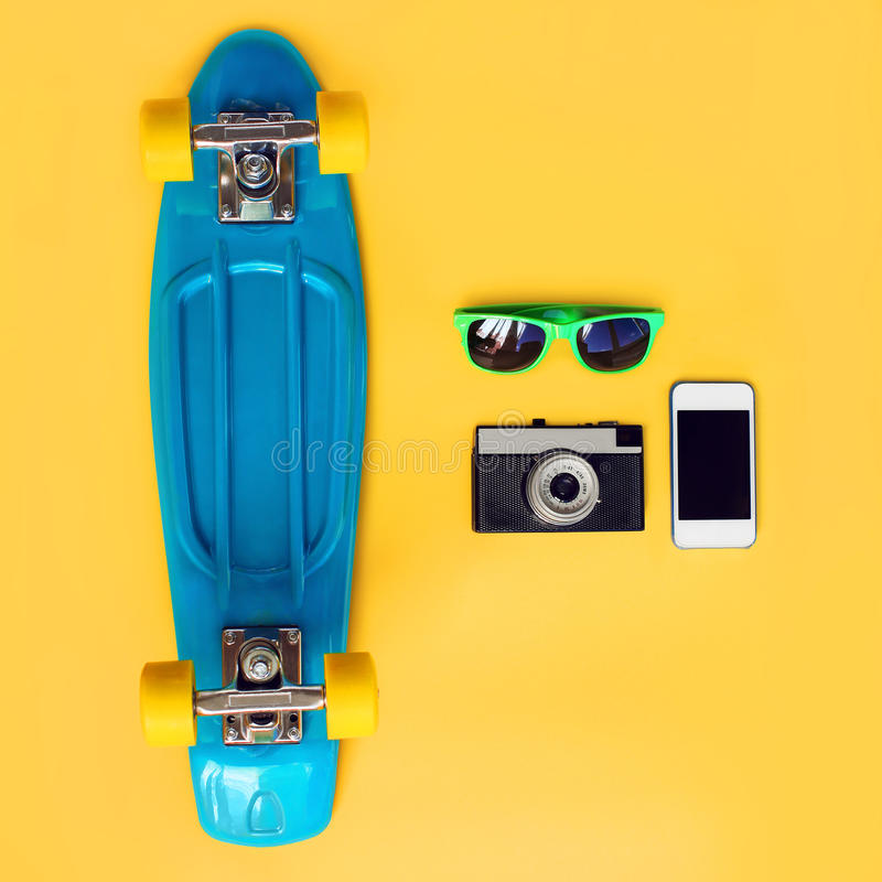 时尚夏天神色概念 蓝色滑板、绿色太阳镜、葡萄酒照相机和屏幕智能手机在黄色背景 图库摄影